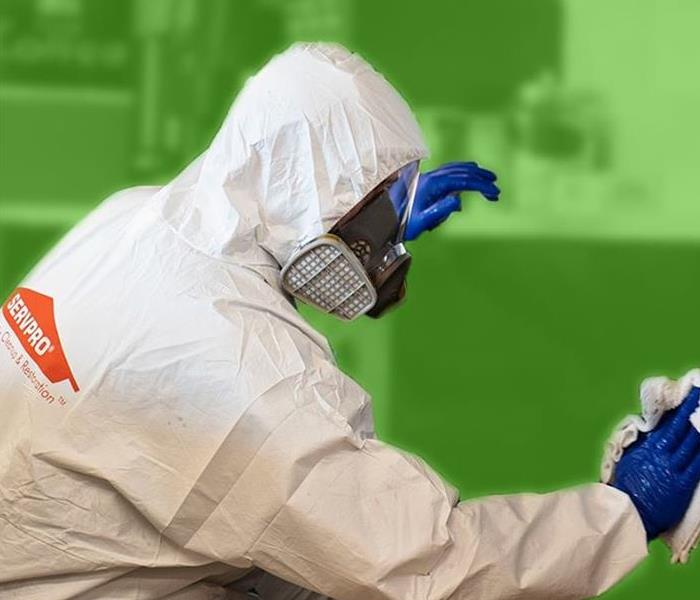 Person dressed in white SERVPRO PPE and blue gloves while cleaning.